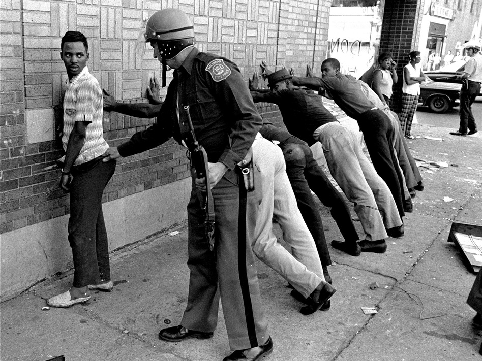 In this photo from July 24, 1967, a police officer searches a youth on Detroit's 12th Street. (AP)