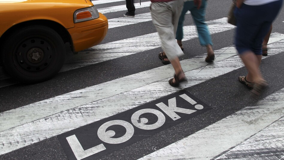 """Pedestrians walk past a """"Look!"""" sign on the crosswalk at the intersection of 42nd Street and Second Avenue in New York. Cities all over the country are looking for ways to get pedestrians to pay more attention. (Seth Wenig/AP)"""