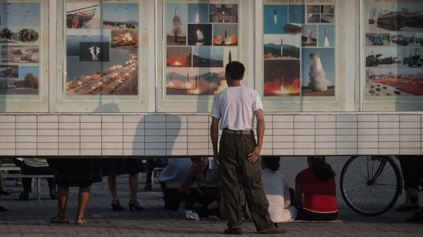 A man looks at images depicting missile launches and military exercises, on a display board in Pyongyang earlier this week.