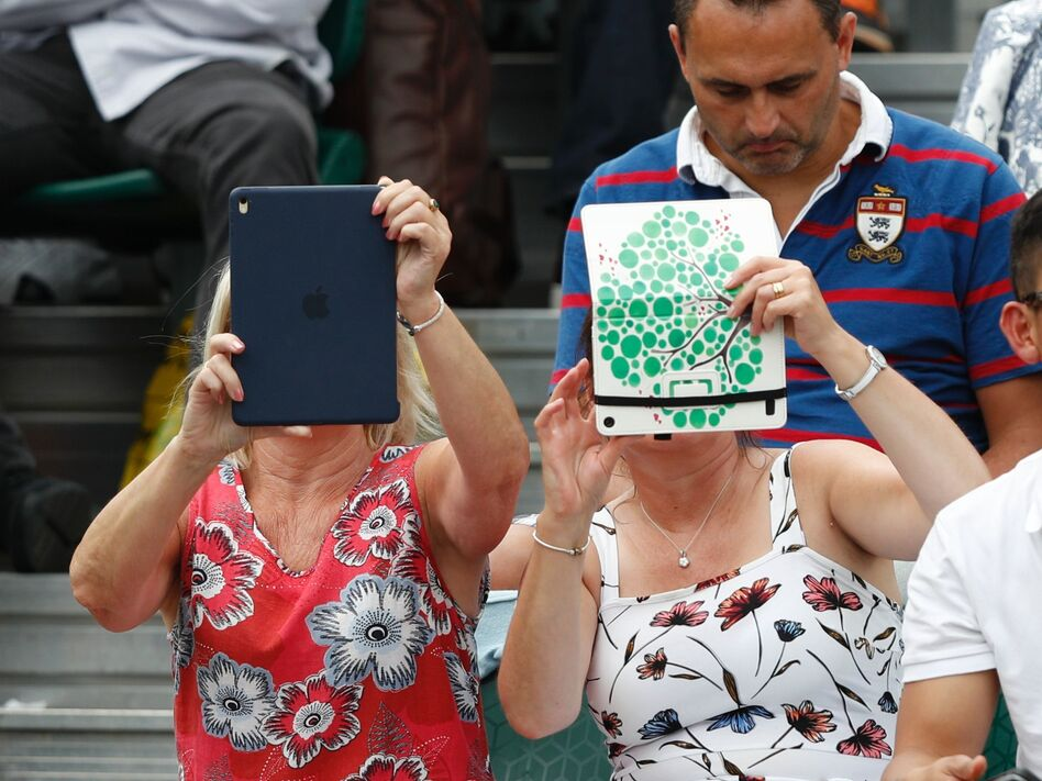 A spectator at Wimbledon last month uses an iPad to take pictures of the action. Improved sales of the tablets were part of the good news out of Apple's quarterly report. (Adrian Dennis/AFP/Getty Images)
