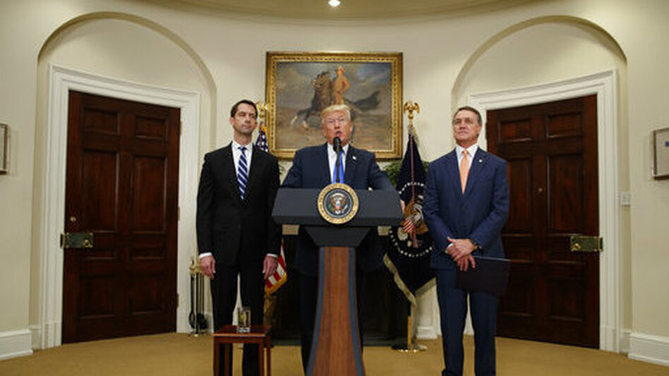 President Trump, flanked by Sens. Tom Cotton, R-Ark. (left), and David Perdue, R-Ga., speaks in the Roosevelt Room of the White House on Wednesday during the unveiling of legislation that would place new limits on legal immigration. (Evan Vucci/AP)