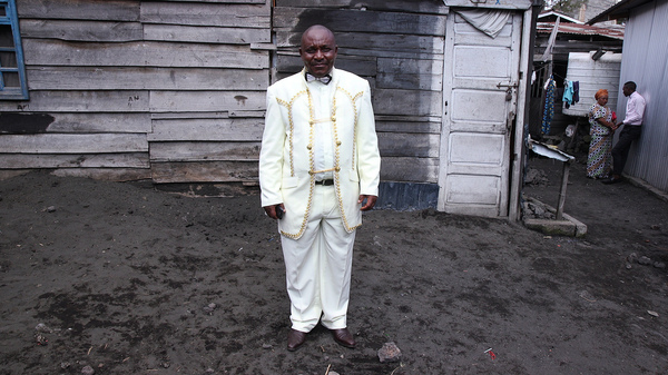 """Theobold Kawa, a 55-year-old pastor, stands outside of AEPL Makedonia church in Goma. He  bought his suit in Uganda. """"I"""