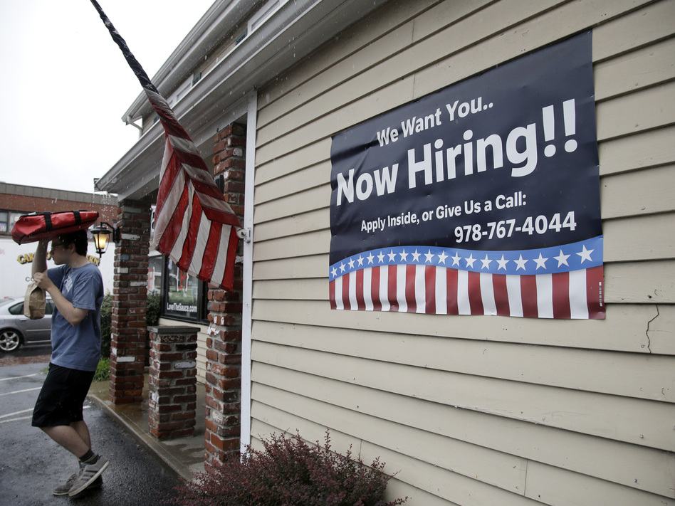 A sign advertising job openings hangs outside a restaurant in Middleton, Mass., last month. At 4.3 percent unemployment, the jobs rate is near the point that most economists deem full employment. (Elise Amendola/AP)