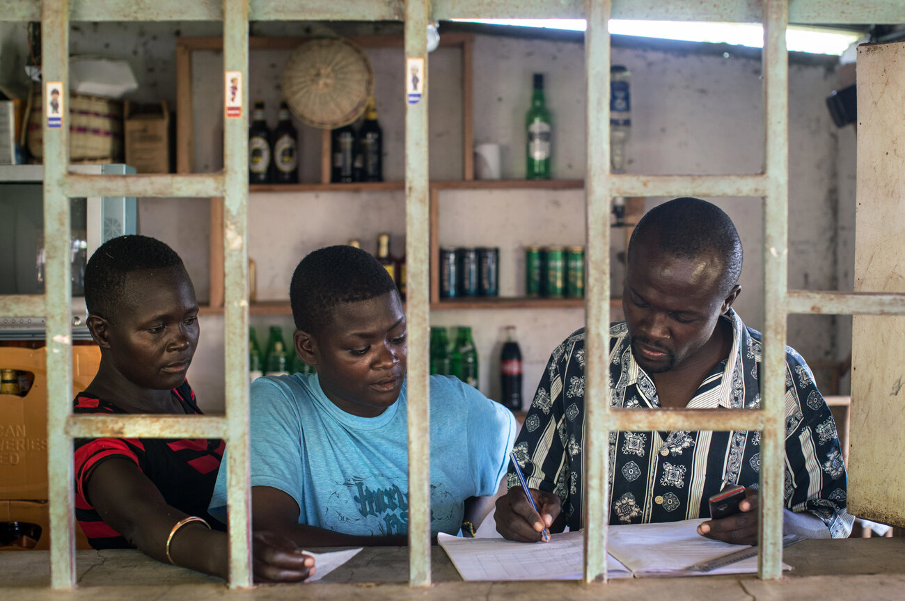 Otieno and two waitresses go over the accounts at his lakeside bar. To start the business he had to take out a loan. Now the payments are crushing him.     (Nichole Sobecki/for NPR)