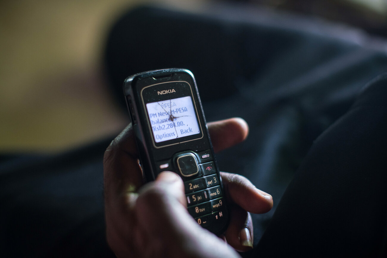 Dancan Odero checks his phone to confirm that the GiveDirectly transfer has been made.     (Nichole Sobecki/for NPR)