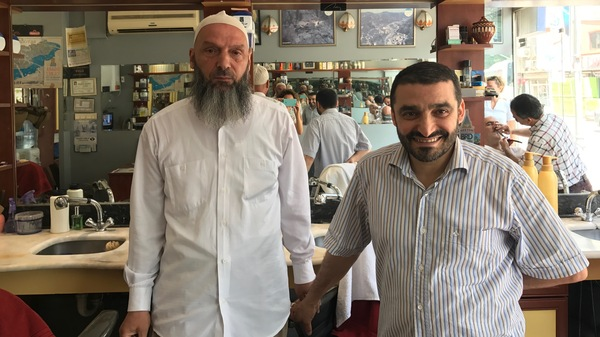 Suat Keceli, left, a retired stockroom worker, and his barber Yasar Ayhan pose in Ayhan