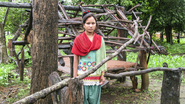 """Kamala stands in front of the hut where she sleeps when she has her period. She lives in western Nepal and was 14 when the photo was taken for an NPR story. She told us: """"I"""
