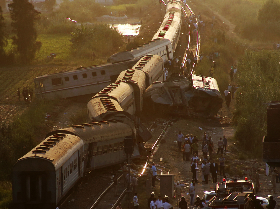Passengers gather beside the tracks after a train crash that killed more than 40 people outside Alexandria. Officials say it's Egypt's deadliest rail accident in years.