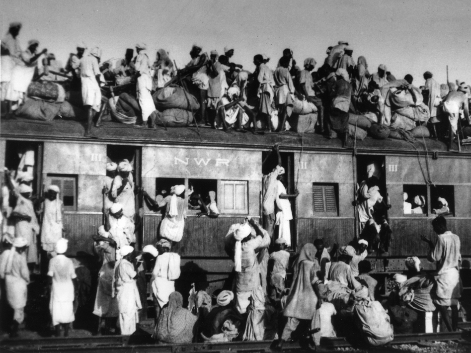 """Muslim refugees crowd onto a train as they try to flee India near New Delhi in September 1947. Some 15 million people crossed new borders during the violent partition of British-ruled India. At times, mobs targeted and killed passengers traveling in either direction; the trains carrying their corpses became known as """"ghost trains."""" (AP)"""