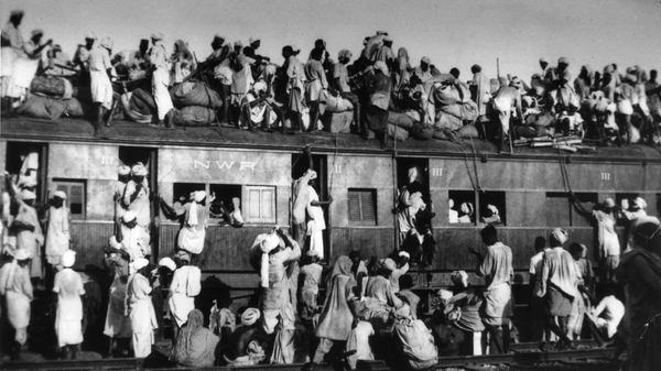"Muslim refugees crowd onto a train as they try to flee India near New Delhi in September 1947. Some 15 million people crossed new borders during the violent partition of British-ruled India. At times, mobs targeted and killed passengers traveling in either direction; the trains carrying their corpses became known as ""ghost trains."""