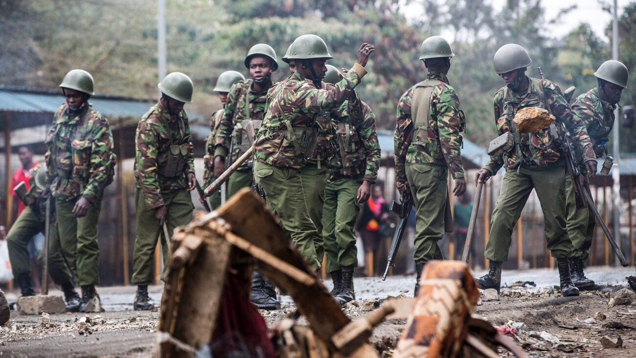 Kenyan police officers clear debris from a barricaded road Friday after an opposition protest roiled a Nairobi neighborhood.     (Luis Tato/AFP/Getty Images)