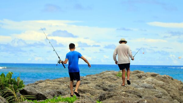 Residents go fishing near Tumon beach on the island of Guam on August 11, 2017. Tourism-dependent Guam is looking to cash in on its new-found fame as a North Korean missile target, tapping an unlikely promotional opportunity to attract visitors to the idyllic island and prove that all publicity is good publicity.