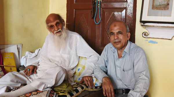 107-year-old Mirza Naseem Changezi (left) sits with his son Khalid Changezi, 60, at their home in the Old City of New Delhi. Changezi is reputed to be the Old City