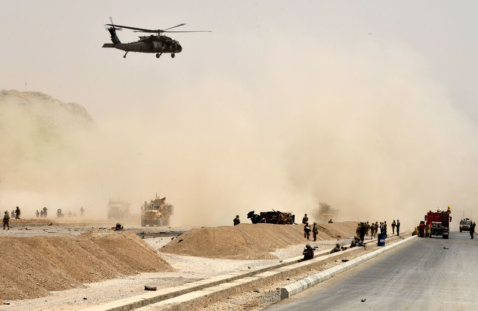 A Black Hawk helicopter flies over the site of a Taliban suicide attack in Kandahar, Afghanistan, on Aug. 2. (Javed Tanveer/AFP/Getty Images)