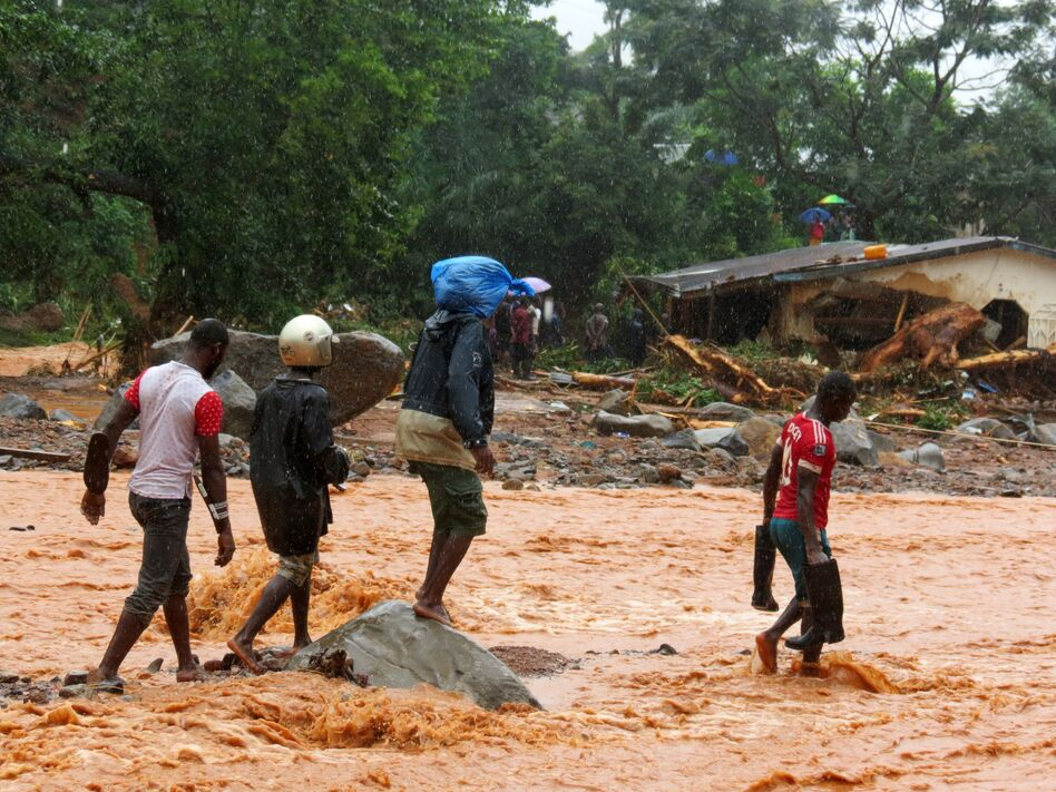Residents pass a damaged building as they walk through floodwaters on the outskirts of Sierra Leone's capital, Freetown, on Monday. (Saidu Bah /AFP/Getty Images)