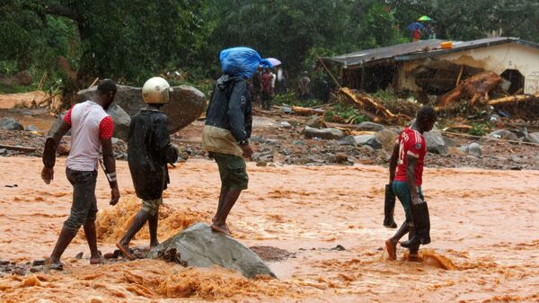 Residents pass a damaged building as they walk through floodwaters on the outskirts of Sierra Leone
