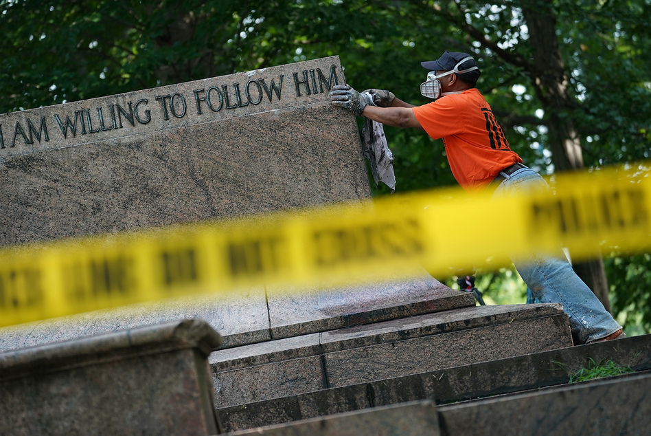 """Baltimore city workers remove graffiti from the pedestal where a statue dedicated to Robert E. Lee and Thomas """"Stonewall"""" Jackson stood on Wednesday. The City of Baltimore removed four statues celebrating confederate heroes from city parks overnight, following the weekend's violence in Charlottesville, Va. (Win McNamee/Getty Images)"""