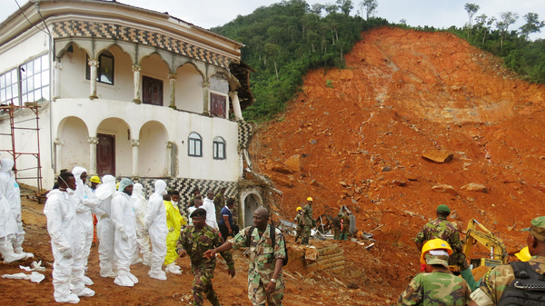 Search and rescue team members and soldiers work near a mudslide site and a damaged building near Freetown, Sierra Leone, on Aug. 15.