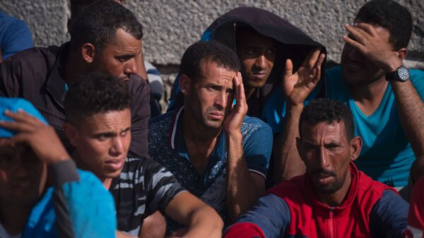 Migrants rest after being rescued in the waters of the Strait of Gibraltar, in the port of Tarifa, on Wednesday.