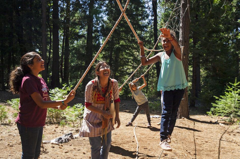 Sofia Majed (from left), Samah Safiullah and Noa Turk assist Fatima Diallo as she navigates the ropes course.