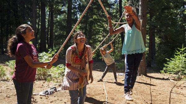 Sofia Majed (left), Samah Safiullah and Noa Turk assist Fatima Diallo as she navigates the ropes course at the Muslim Youth Camp of California.