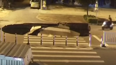 WATCH: Distracted Driver Hits Sinkhole, Fails To Mind The Gap