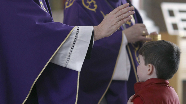 A priest blesses a boy during Holy Communion. Earlier this year, the Irish Catholic Bishops