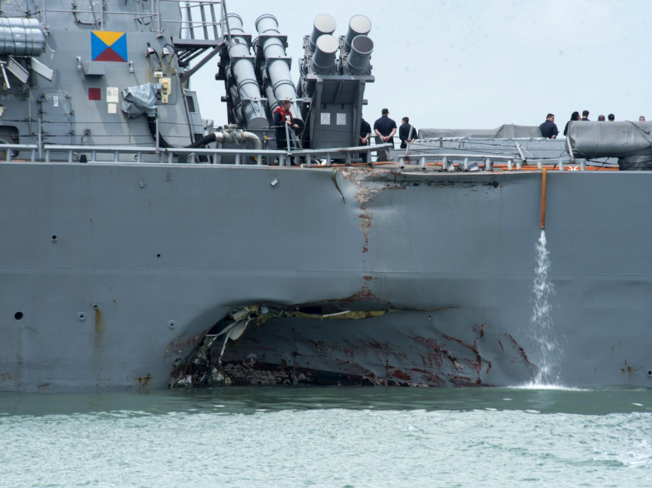 Damage to the port side is visible as the guided-missile destroyer USS John S. McCain steers toward Changi naval base in Singapore following a collision with the merchant vessel Alnic MC on Monday. (Mass Communication Specialist 2nd Class Joshua Fulton/AP)