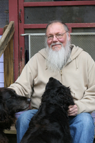 Gray Zeitz sits on his porch with his two dogs.