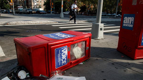A Village Voice newspaper stand lays on the ground next to garbage in New York City