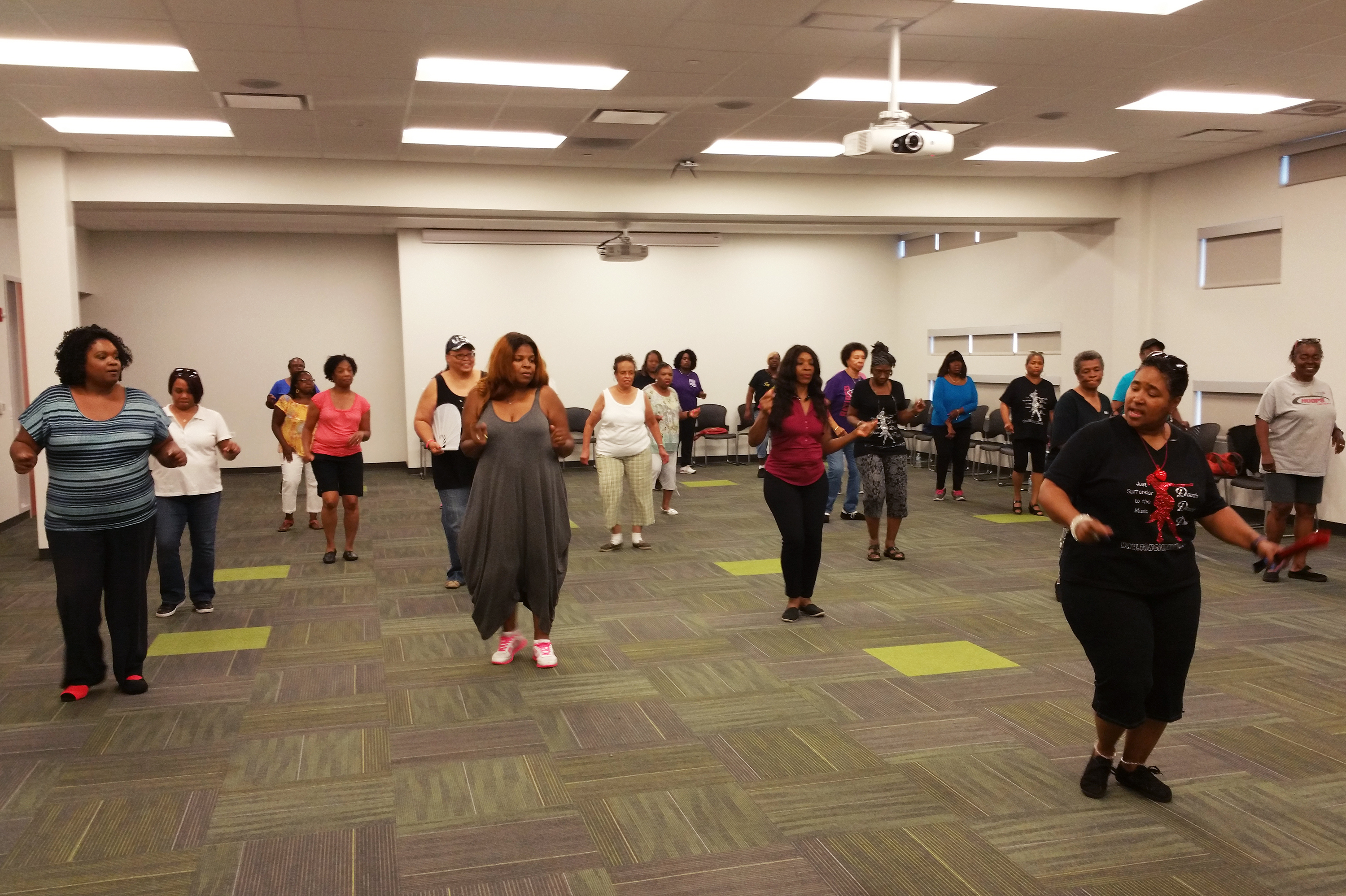 Dawn, 'the Dancin' Deeva,' helps a group of women learn new moves during an adult line dancing class. The Harvey Library offers the free class weekly. (Cheryl Corley/NPR)