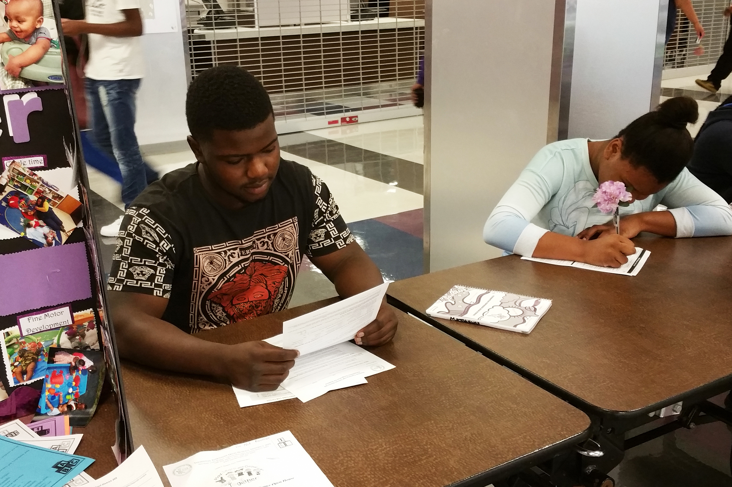 Derius Matthews, 17, fills out forms on registration day. He says he's ready for his senior year — and Thorton High's football season — to start. (Cheryl Corley/NPR)