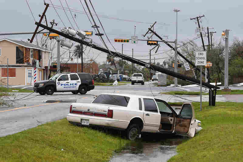 A care lies abandoned and power lines are broken after heavy damage from Harvey in Rockport, Texas.