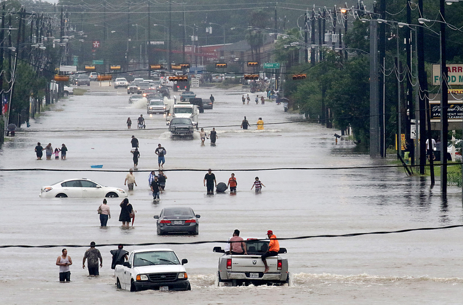 People walk through the flooded waters of Telephone Rd. in Houston as the fourth largest city in the U.S. battles Tropical Storm Harvey and resulting floods. (Thomas B. Shea/AFP/Getty Images)