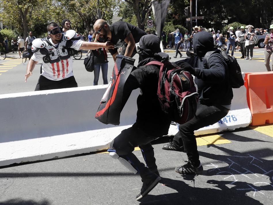 Patriot Prayer founder Joey Gibson (second from left) is chased by anti-fascists during a Rally Against Hate on Sunday in Berkeley, Calif. (Marcio Jose Sanchez/AP)