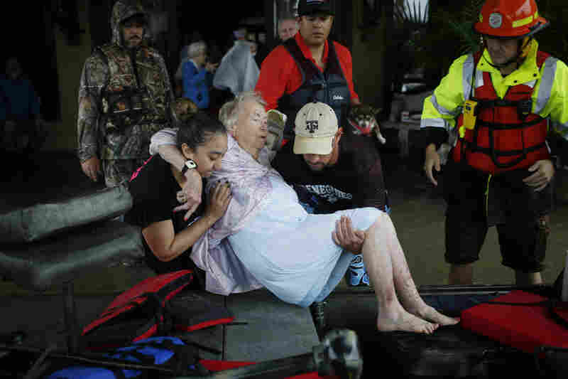 Rescuers help a woman from a flooded retirement home into a boat after Hurricane Harvey in Spring, Texas, on Monday. A deluge of rain and rising floodwaters left Houston immersed.