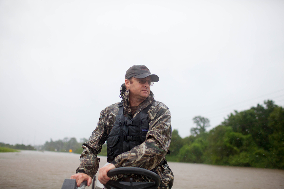 Troy King navigates his boat through a flooded portion of Highway 90 in Houston on his way to rescue the Galvan family. (Katie Hayes Luke for NPR)