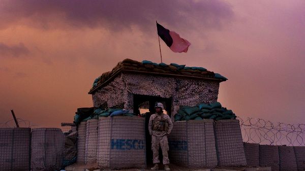 A U.S. Marine looks out as an evening storm gathers above an outpost near Kunjak, in southern Afghanistan