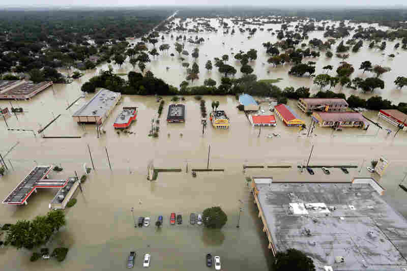 Water from Addicks Reservoir flows into neighborhoods as floodwaters from Hurricane Harvey rise on Tuesday in Houston. Harvey dumped nearly 52 inches of rain at one location east of Houston, the National Weather Service said.