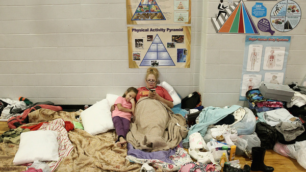 Christine Garcia relaxes with her 8-year-old daughter Mia in the Channelview High School gym. It