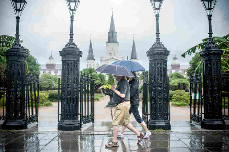 People walk along Jackson Square in New Orleans on Wednesday under some light rain. A flood advisory was issued for New Orleans area until 8:30 p.m tonight.