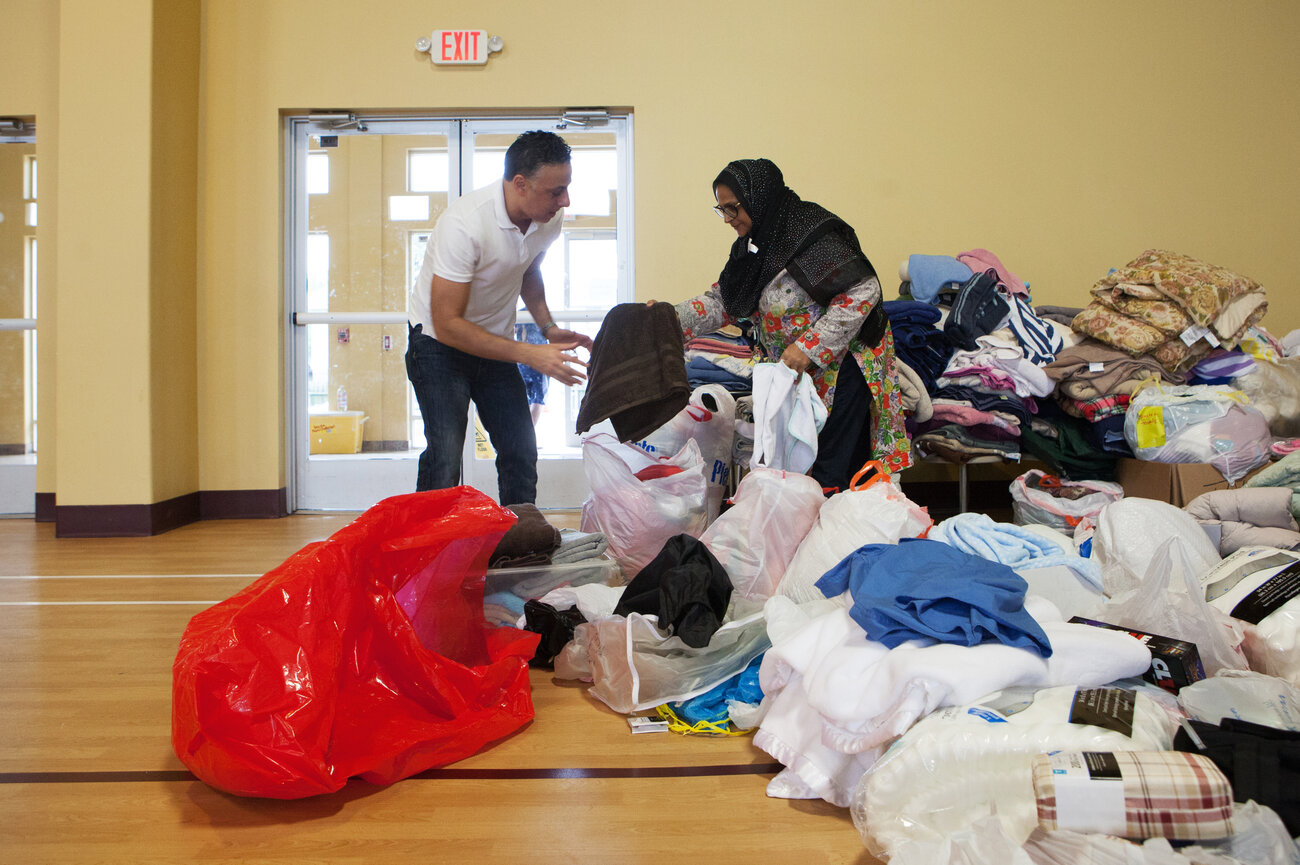Kasin helps sort through the many donations that the mosque received. (Claire Harbage/NPR)