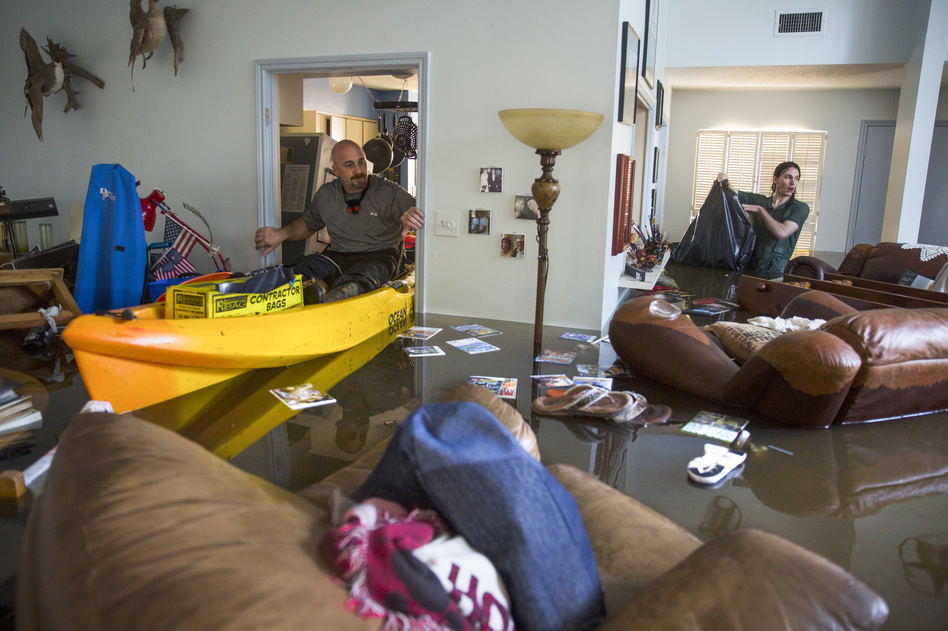 Larry Koser Jr. (left) and his son, Matthew, look for important papers and heirlooms inside his house after it was flooded by heavy rains from Hurricane Harvey. (Erich Schlegel/Getty Images)