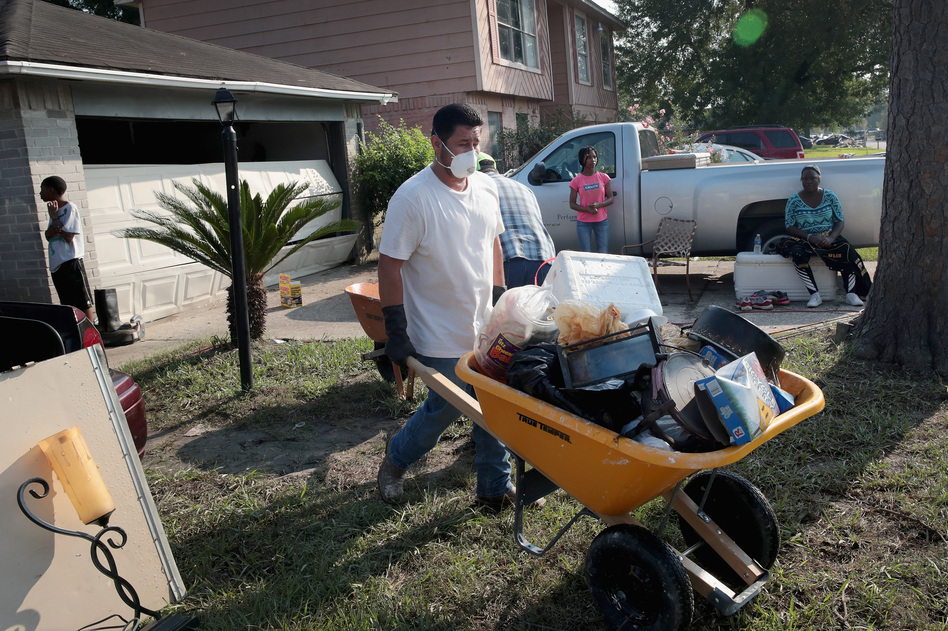 Volunteers from Performance Contractors help co-worker Cornell Beasley deal with Harvey-related water damage to his home in Houston on Friday. (Scott Olson/Getty Images)