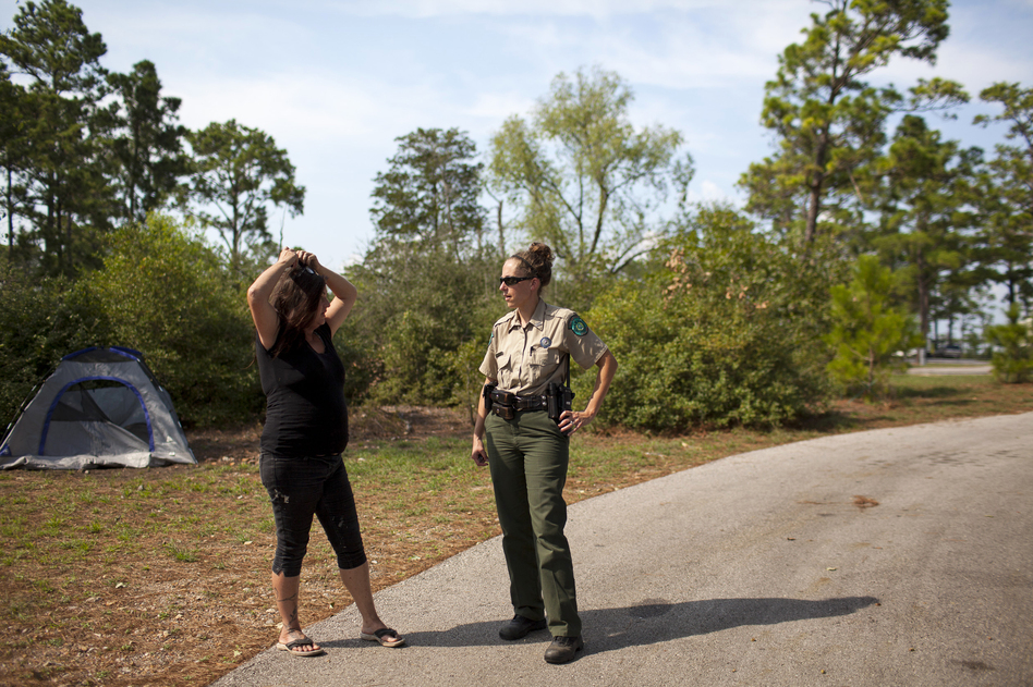 Susan Arawley (left) speaks with Jamie Creacy, superintendent of the Lost Pines Complex, which includes Bastrop State Park. As Hurricane Harvey hit, Arawley tried picking up supplies and got stuck in rising flood water. After sleeping in her car four nights, she decided to head to Bastrop State Park, where she could take a shower. (Katie Hayes Luke for NPR)