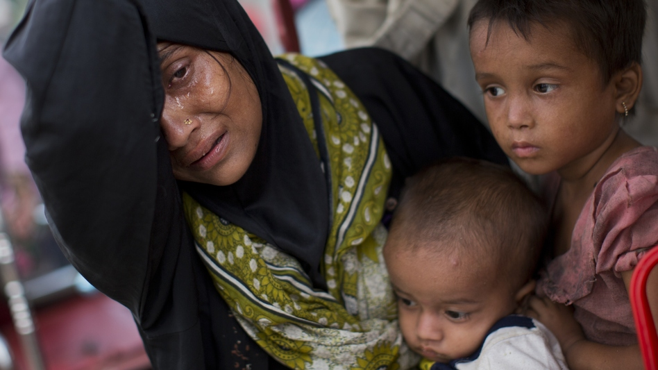 A Rohingya woman rests for a moment with her children Tuesday after crossing into Bangladesh. She says she lost several members of her family in Myanmar, where a new spate of violence has sent more than 100,000 Rohingya Muslims fleeing what they describe as certain death. (Bernat Armangue/AP)
