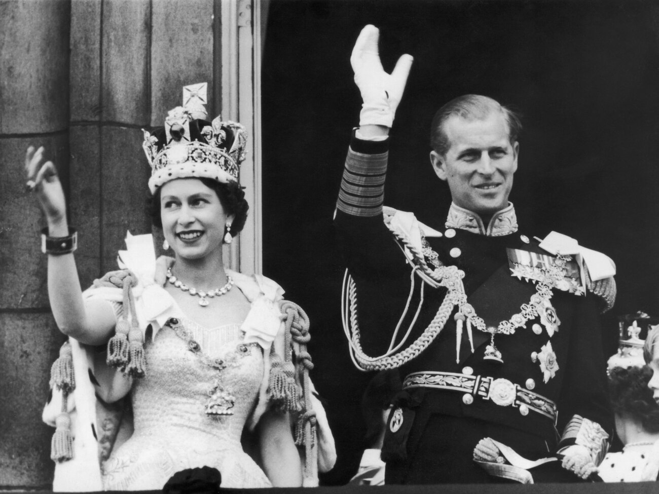 Queen Elizabeth II and the Duke of Edinburgh wave at the crowds from the balcony at Buckingham Palace on June 2, 1953. (Keystone/Getty Images)