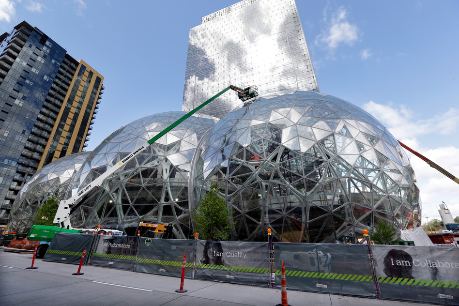 Amazon said Thursday that it will spend $5 billion to build another headquarters in North America to house 50,000 new employees. In April, workers constructed three glass-covered domes in an expansion of the company's downtown Seattle campus. (Elaine Thompson/AP)