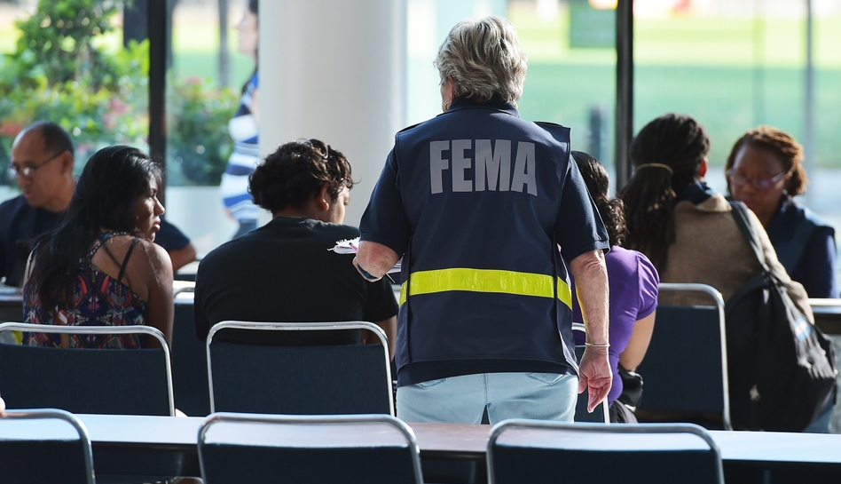 An official with the Federal Emergency Management Agency talks to people at Houston's George R. Brown Convention Center, which has been a shelter for evacuees from Hurricane Harvey, on Sept. 2. (Mandel Ngan/AFP/Getty Images)
