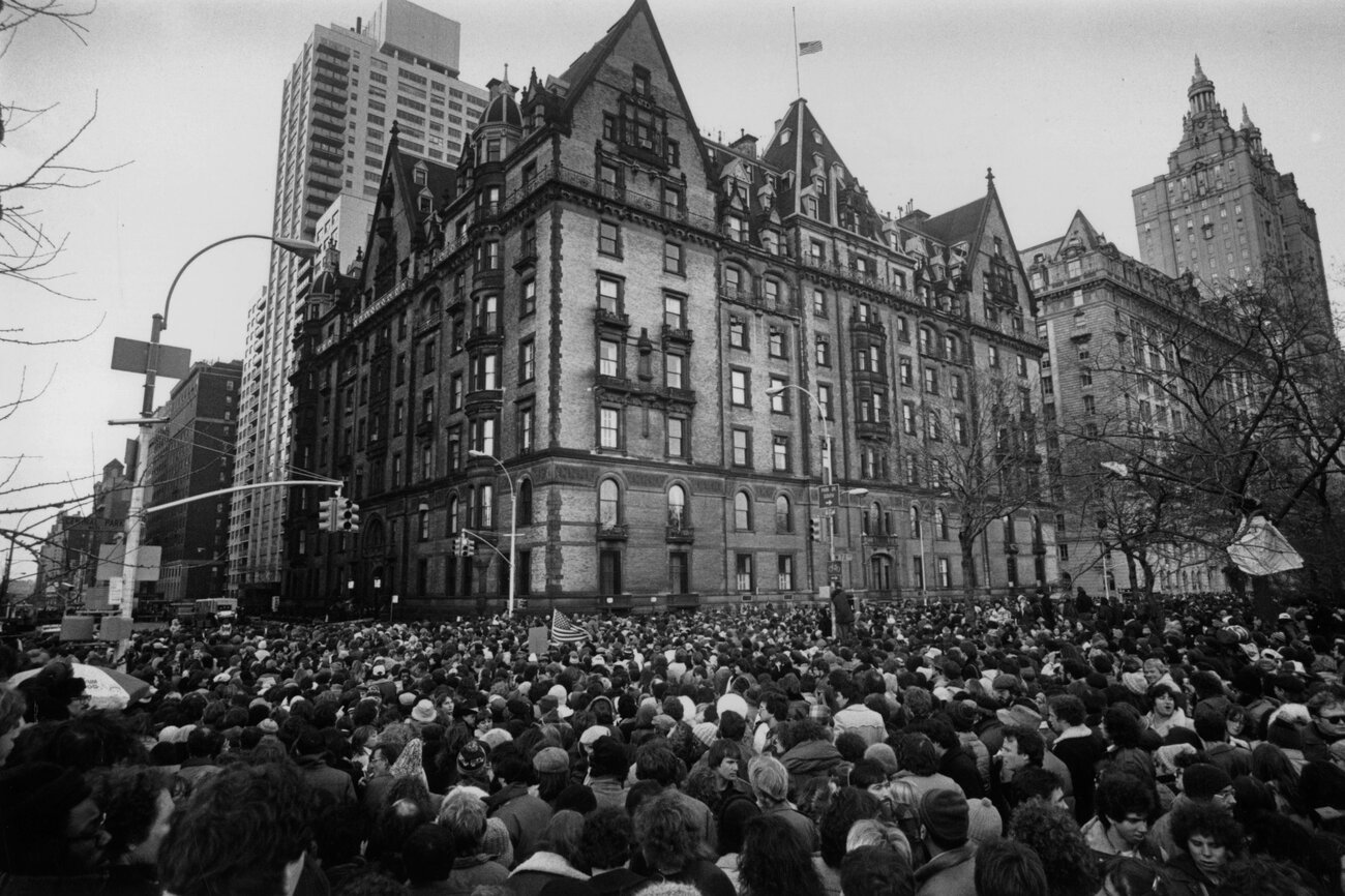 Crowds gathered outside the home of John Lennon in New York City on Dec. 9, 1980, after hearing that he had been shot and killed. A flag flies at half-staff over the building. (Keystone/Getty Images)